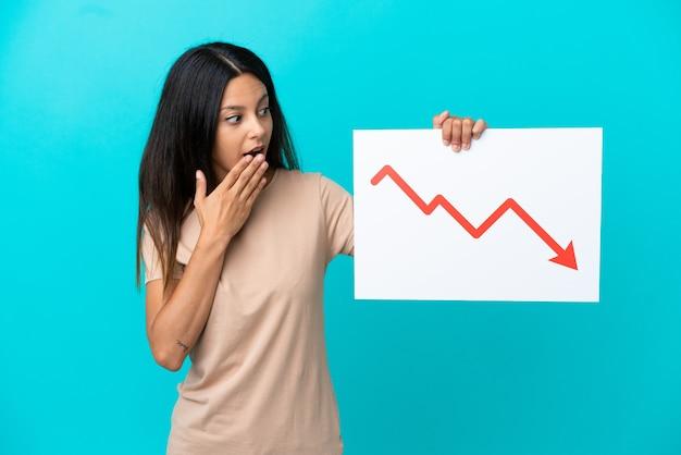 Mulher jovem segurando um fundo isolado com uma expressão de surpresa e um símbolo de seta decrescente de estatísticas