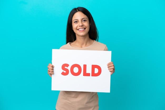 Mulher jovem segurando um fundo isolado segurando um cartaz com o texto vendido com uma expressão feliz