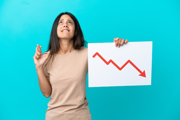 Mulher jovem segurando um fundo isolado segurando uma placa com um símbolo de seta de estatísticas decrescentes e cruzando os dedos