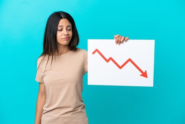 Mulher jovem segurando um fundo isolado segurando uma placa com um símbolo de seta decrescente de estatísticas com uma expressão triste