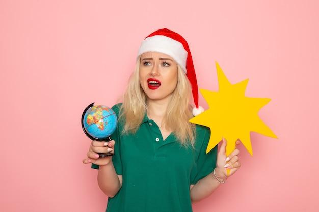 Mulher jovem segurando um globo e uma figura amarela na parede rosa foto modelo mulher de frente para o feriado de natal