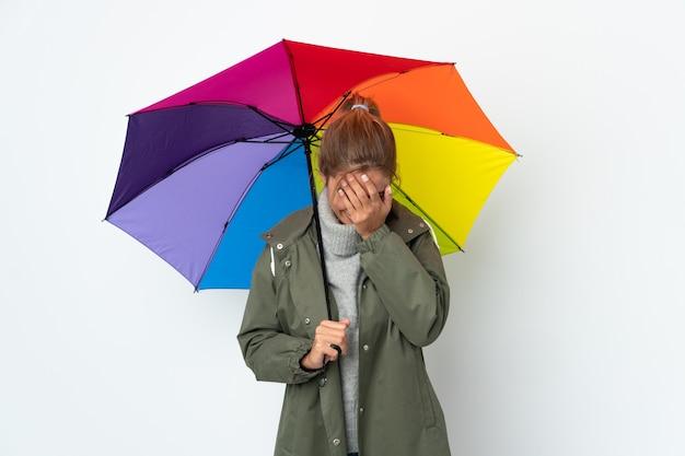 Mulher jovem segurando um guarda-chuva no fundo branco com uma expressão cansada e doente