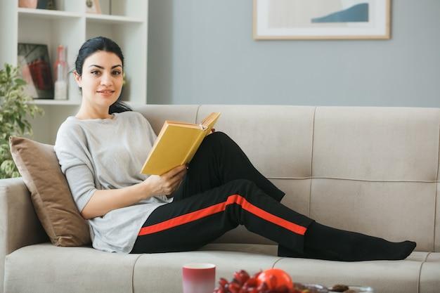 Mulher jovem segurando um livro deitado no sofá atrás da mesa de centro na sala de estar