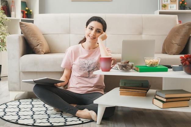Mulher jovem segurando um livro sentado no chão atrás da mesa de centro na sala de estar