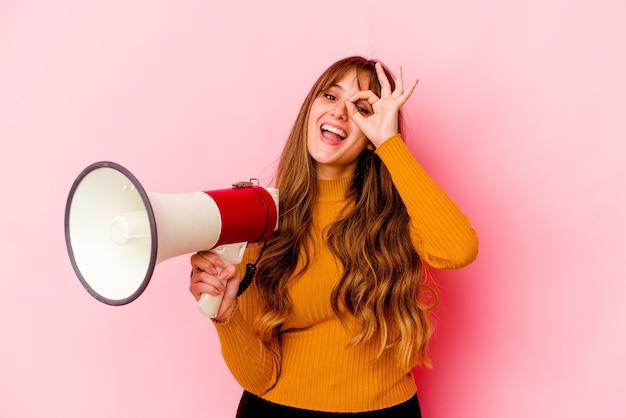 Mulher jovem segurando um megafone isolado animada mantendo um gesto de ok no olho