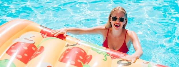 Mulher jovem, segurando, um, pizza, natação, flutuador