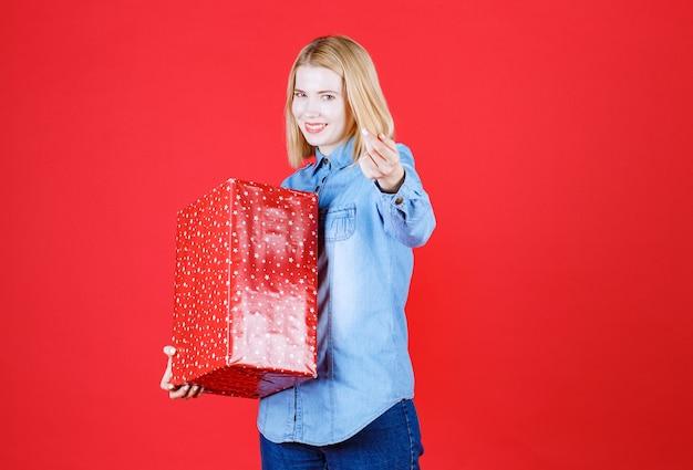 Mulher jovem segurando um presente de aniversário e fazendo gestos deliciosos