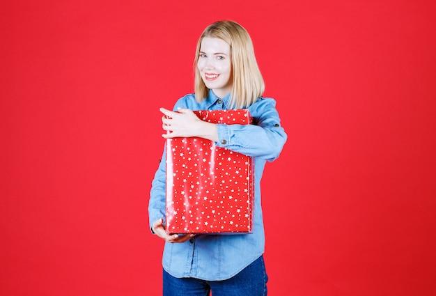 Mulher jovem segurando um presente de aniversário e sorrindo