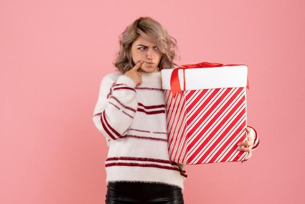 Mulher jovem segurando um presente de natal de frente com uma cara confusa