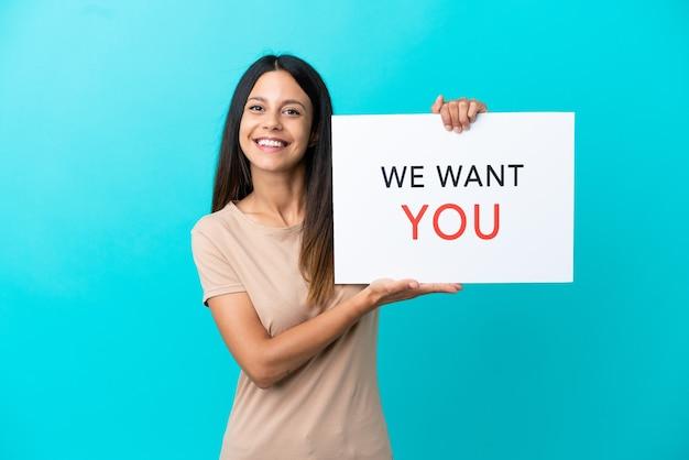 Mulher jovem segurando um quadro do we want you com uma expressão feliz em um fundo isolado.