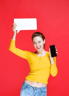 Mulher jovem segurando um quadro retangular de informações e um smartphone preto