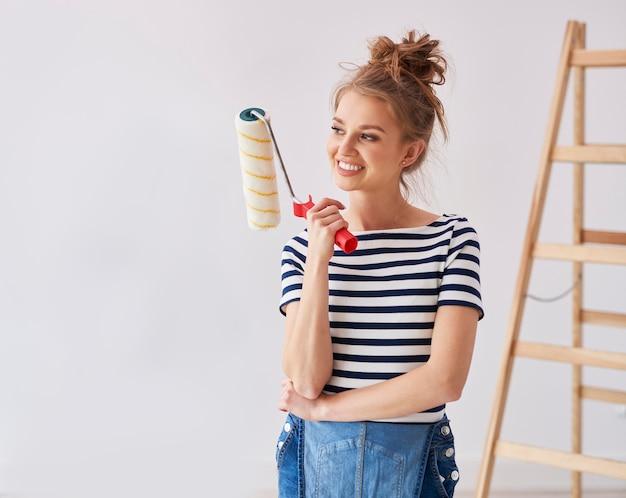 Mulher jovem segurando um rolo de pintura