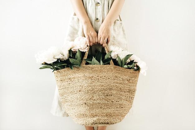 Mulher jovem segurando um saco de palha com flores de peônia branca na superfície branca