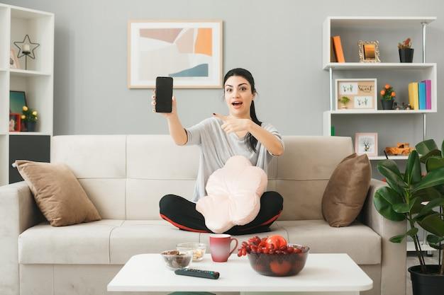 Mulher jovem segurando uma almofada e aponta para o telefone, sentada no sofá atrás da mesa de centro na sala de estar