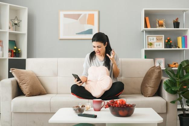 Mulher jovem segurando uma almofada, olhando para o telefone, sentada no sofá atrás da mesa de centro na sala de estar