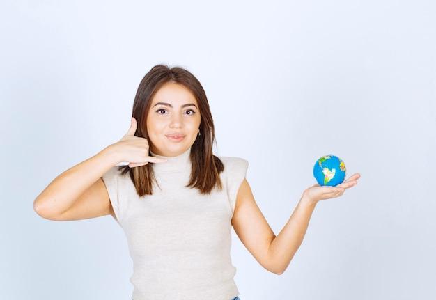Mulher jovem segurando uma bola do globo terrestre e fazendo um sinal de chamada