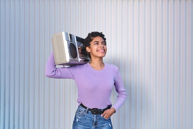 Mulher jovem segurando uma caixa de som, ouvindo música e parece positiva