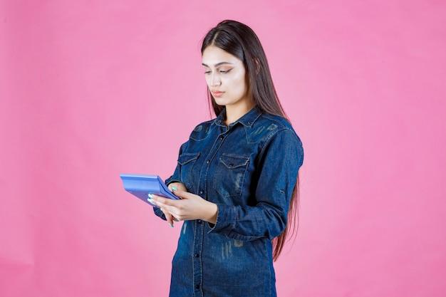 Mulher jovem segurando uma calculadora azul na mão e calculando