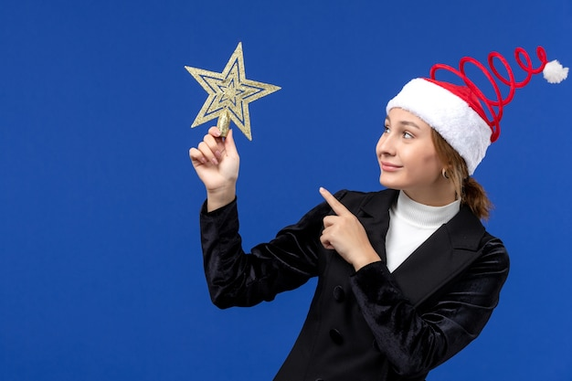 Mulher jovem segurando uma decoração em forma de estrela de frente em uma parede azul no feriado de ano novo
