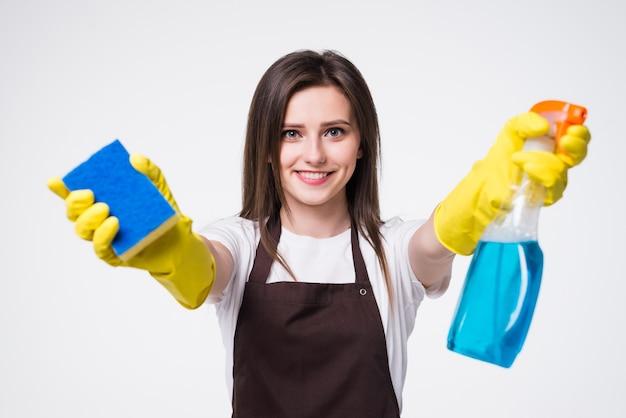 Mulher jovem segurando uma esponja e um produto de limpeza