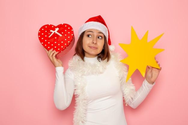 Mulher jovem segurando uma figura amarela e presente na parede rosa neve cor de natal feriado ano novo