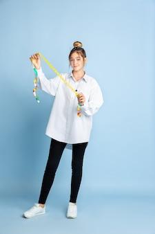 Mulher jovem segurando uma fita métrica