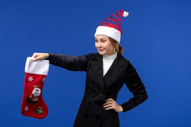 Mulher jovem segurando uma grande meia de natal na mesa azul, feriado de véspera de ano novo, vista frontal