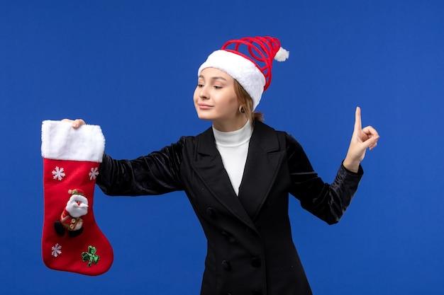 Mulher jovem segurando uma grande meia de natal na parede azul-clara, no feriado de véspera de ano novo, vista frontal
