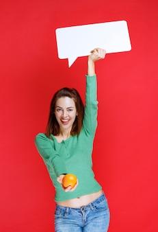 Mulher jovem segurando uma laranja fresca e um painel de informações retângulo e oferecendo a laranja ao cliente