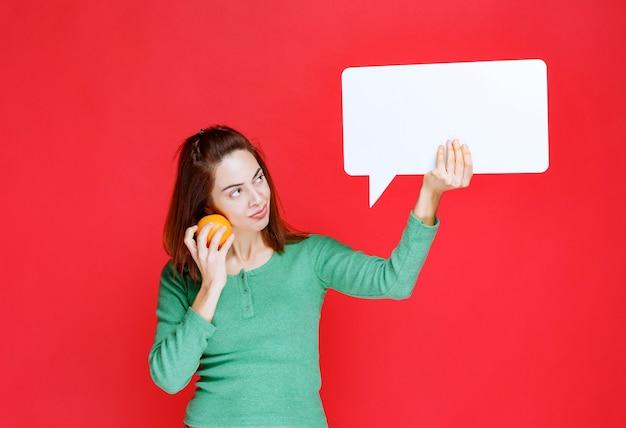 Mulher jovem segurando uma laranja fresca e um painel de informações retângulo e parece pensativa