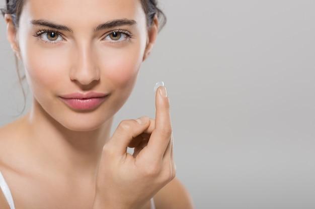 Mulher jovem segurando uma lente de contato no dedo indicador com espaço de cópia