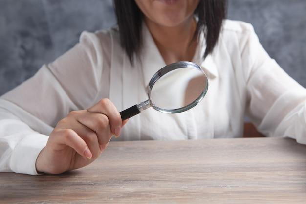 Mulher jovem segurando uma lupa ao lado da mesa