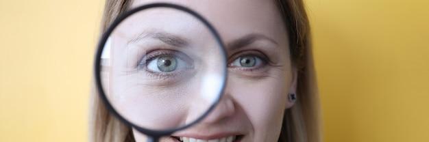 Mulher jovem segurando uma lupa perto do olho