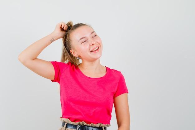 Mulher jovem segurando uma mecha de cabelo em uma camiseta e calças e parece feliz
