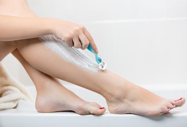 Mulher jovem segurando uma navalha e barbeando as pernas no banheiro