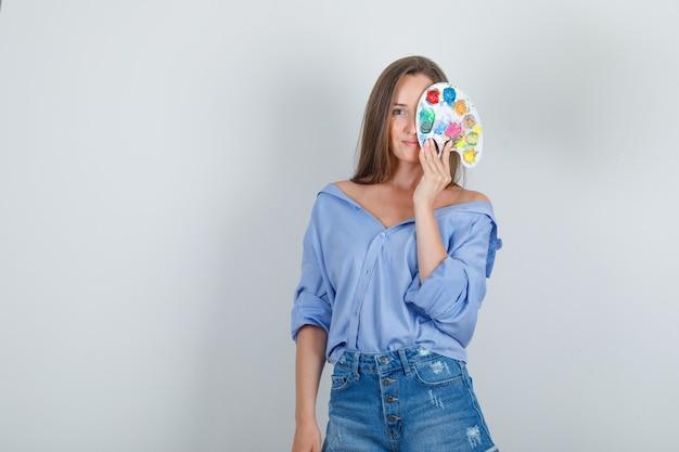 Mulher jovem segurando uma paleta de arte sobre um olho em uma camisa azul