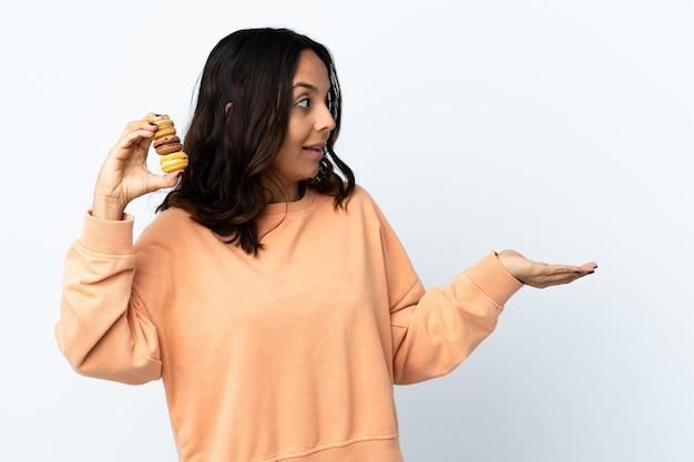 Mulher jovem segurando uma parede branca isolada segurando macarons franceses coloridos e com expressão de surpresa