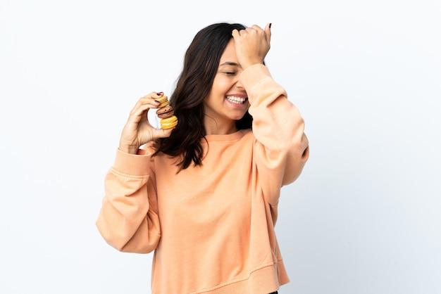 Mulher jovem segurando uma parede branca isolada segurando macarons franceses coloridos e tentando encontrar a solução