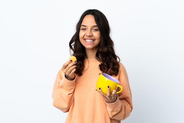 Mulher jovem segurando uma parede branca isolada segurando macarons franceses coloridos e um copo de leite