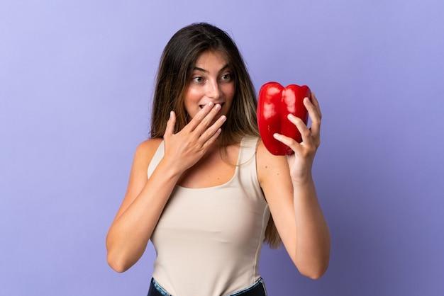 Mulher jovem segurando uma pimenta isolada no roxo com expressão facial surpresa e chocada