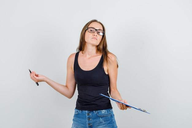 Mulher jovem segurando uma prancheta e uma caneta em camiseta, shorts, óculos e parecendo confiante