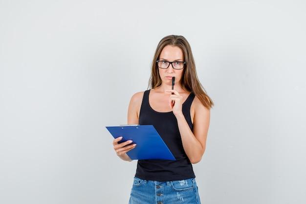 Mulher jovem segurando uma prancheta e uma caneta em camiseta, shorts, óculos e parecendo pensativa