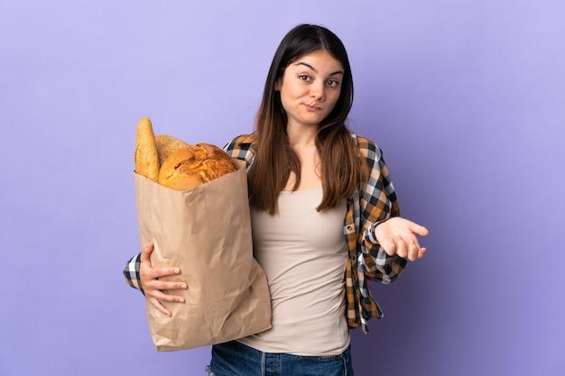 Mulher jovem segurando uma sacola cheia de pães isolada na parede roxa, fazendo gestos de dúvida enquanto levanta os ombros