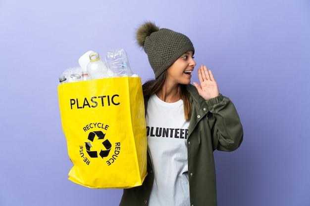 Mulher jovem segurando uma sacola cheia de plástico gritando com a boca bem aberta para o lado