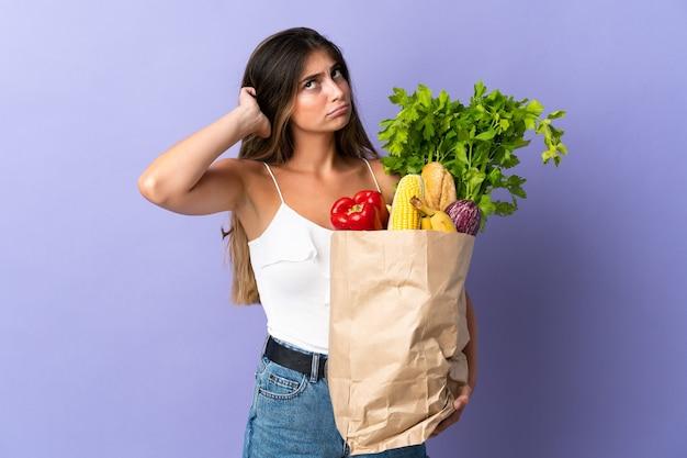 Mulher jovem segurando uma sacola de compras de supermercado e tendo dúvidas