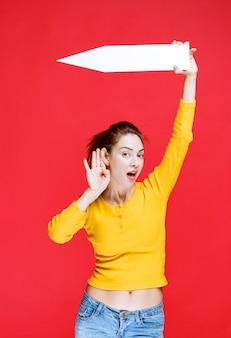 Mulher jovem segurando uma seta apontando para a esquerda e ouvindo com atenção