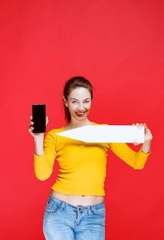 Mulher jovem segurando uma seta apontando para a esquerda e um smartphone preto