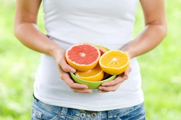 Mulher jovem segurando uma tigela cheia de laranjas e toranjas