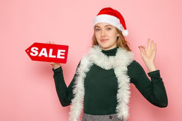 Mulher jovem segurando uma venda vermelha escrita na parede rosa, feriado de ano novo, foto, compras, emoção