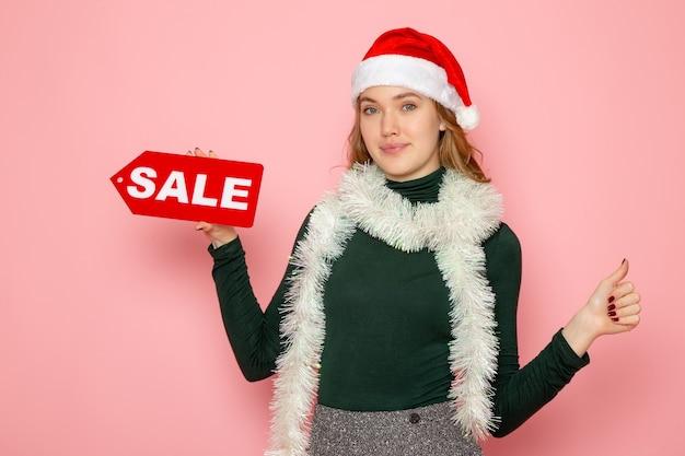 Mulher jovem segurando uma venda vermelha escrita na parede rosa natal feriado ano novo foto compras moda emoção